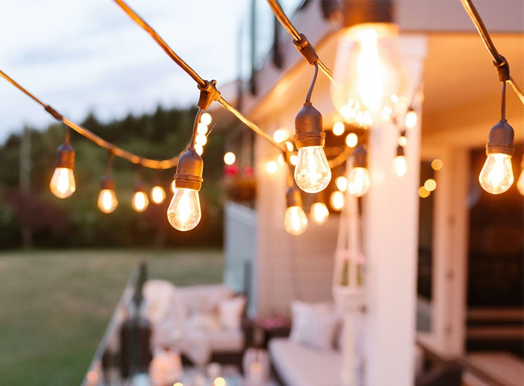 """Light bulbs, hanging along exterior of home"""