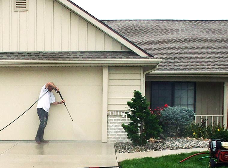 """""""Man pressure washing exterior of home"""""""