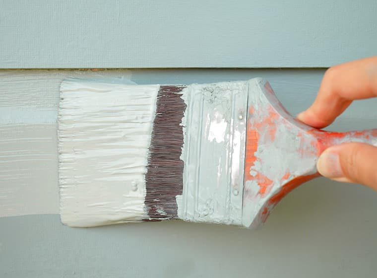 Painting siding with paint brush