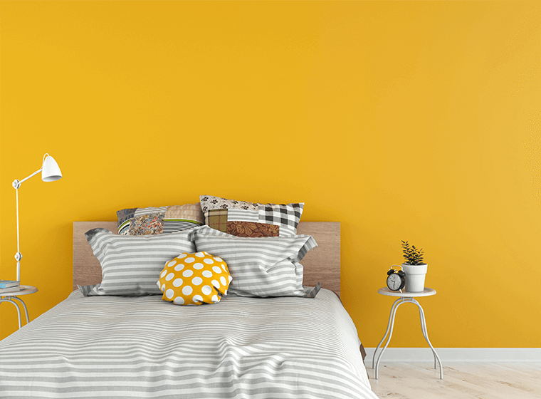 """""""Stripped bed against yellow painted wall"""""""
