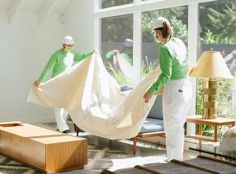 Painters putting down drop cloth before painting
